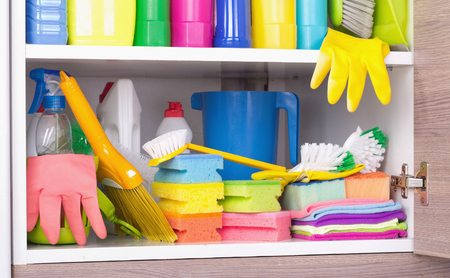Cleaning products and equipment placed in kitchen cabinet. Housekeeping storage space