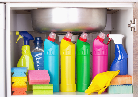 Cleaning products placed in kitchen cabinet under sink. Housekeeping storage space Foto de archivo