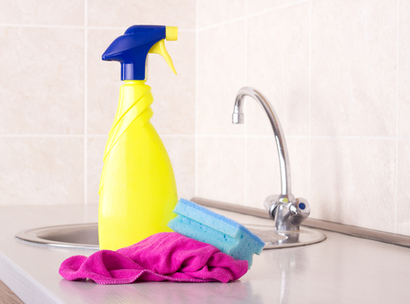 desinfectante: Close up of spray bottle, sponge and cleaning cloth on kitchen countertop with faucet in background. Housekeeping concept