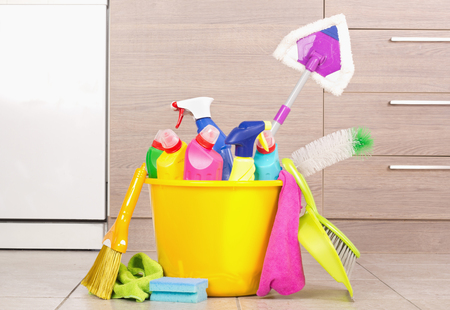 kitchen cabinets: Bucket full of cleaning products and equipment standing on floor in front of kitchen cabinets. Housekeeping concept