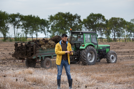 Young farmer with beard holding tablet in front of tractor in field. Seasonal agricultural works Stok Fotoğraf