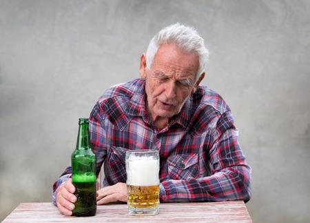 Senior drunk man sitting at table with beer bottle and mug in front of him Standard-Bild