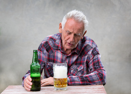 Anziano ubriaco uomo seduto al tavolo con bottiglia di birra e tazza di fronte a lei Archivio Fotografico - 85922101