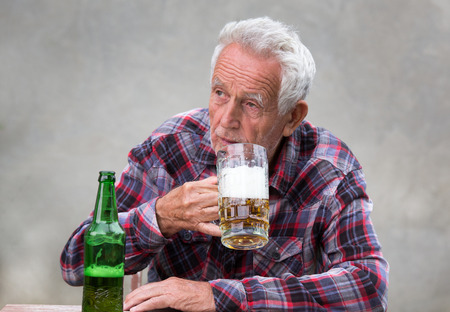 Senior homme assis à table et boire de la bière de la tasse