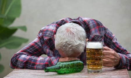Starszy pijany mężczyzna śpi przy stole z butelką piwa i kubek przed nim Zdjęcie Seryjne