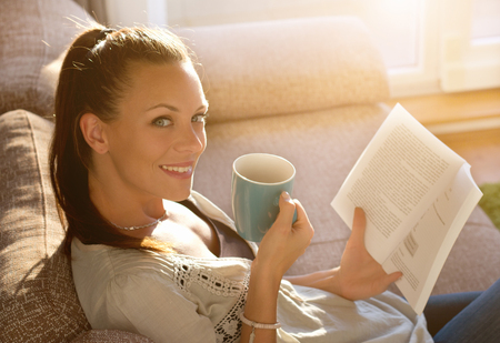 atmosphere: Pretty young girl sitting on sofa, drinking coffee and reading book. Cozy domestic atmosphere on beautiful sunshine