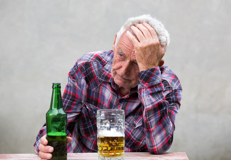 Senior man with hangover holding his head at table with beer bottle and mug in front of him
