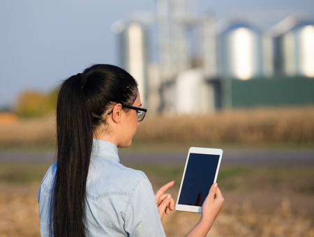 Pretty young woman holding tablet in field with grain silos in background. Agribusiness concept