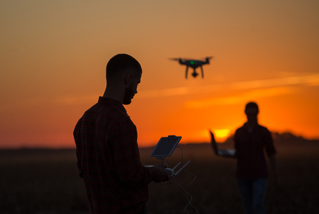 Silueta del drone de navegación del granjero joven sobre tierras de labrantío. Innovaciones de alta tecnología para aumentar la productividad en la agricultura