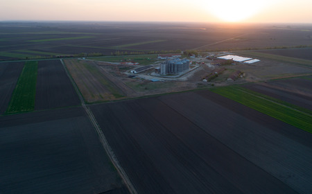 Aerial image of big farm with metal silos for grains storing in plains, shoot from drone