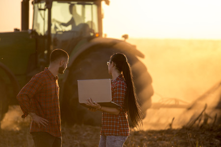 Two young farmers with laptop standing in front of tractor in field at sunset