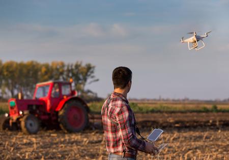Aantrekkelijke landbouwers navigerende hommel boven landbouwgrond. Technologische innovaties voor het verhogen van de productiviteit in de landbouw