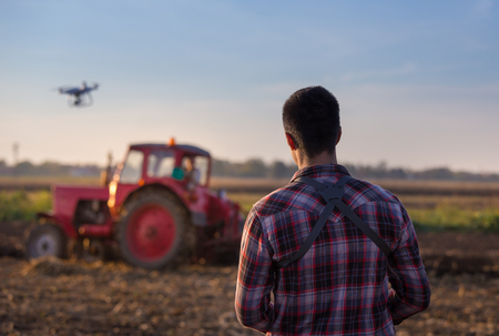 Young farmer navigating drone above farmland. High technology innovations for increasing productivity in agriculture Stock fotó