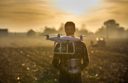 Close up of flying drone and blurred man with remote control in background in field. High technology innovations for increasing productivity in agriculture