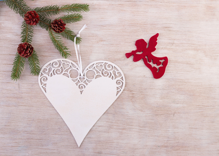 White xmas decoration ornament in heart shape hanging from fir tree and red Angel greeting Christmas holiday. Place for your text Stock Photo