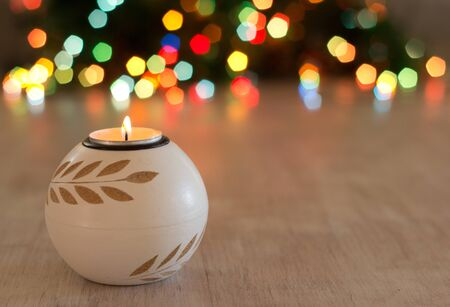 Close up of candle burning on wooden table and colorful lights in background. Christmas and New year holiday concept Stock Photo