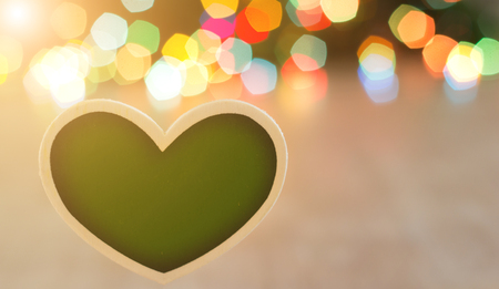 Close up of heart shape board in front of colorful lights. Christmas and New Year holiday concept. Place for your text