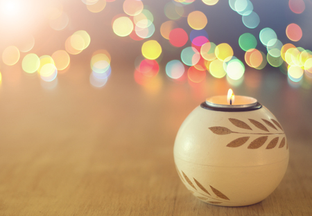 Close up of candle burning on wooden table and colorful lights in background. Christmas and New year holiday concept 스톡 콘텐츠