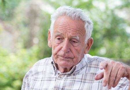 Portrait of sad senior man sitting in park and looking at one spot Standard-Bild