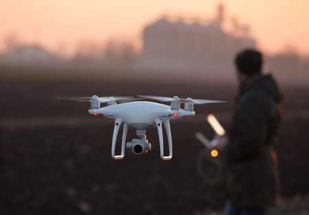 Farmer navigating drone above farmland with silos in background. High technology innovations for increasing productivity in agriculture Stock Photo