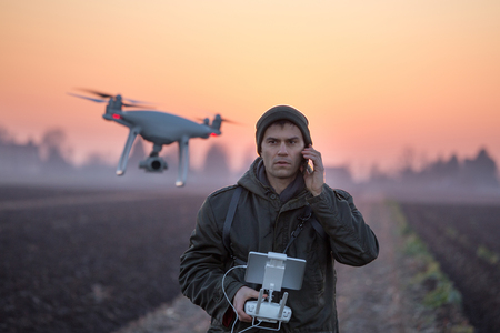 Navigating drone above farmland with silos