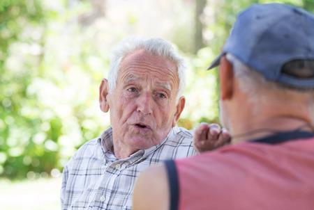 공원에서 그의 친구와 이야기하는 수석 남자의 초상 스톡 콘텐츠