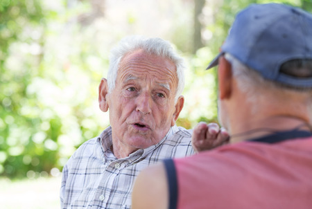 Portrait of senior man talking to his friend in park