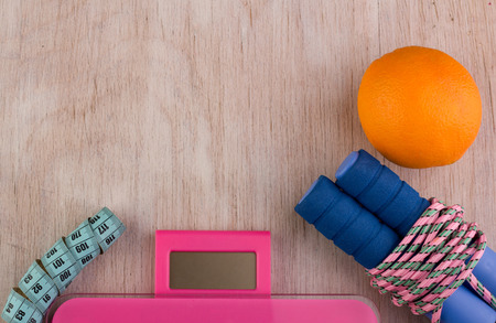 Top view of jumping rope, scale, measuring tape and orange fruit on wooden background. Fitness and dieting concept