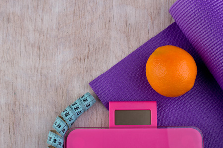 Top view of yoga mat, scale, measuring tape and orange fruit on wooden background. Fitness and dieting concept