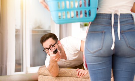 Lazy man with remote control trying to watch tv behind wife with laundry basket. Woman doing chores while man resting