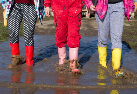Three young girls in colorful gumboots walking in puddle. Shoes for extreme rainy weather conditions