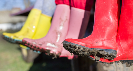 Close up of muddy gumboots in different colors. Three girls sitting with crossed legs and showing dirty shoes