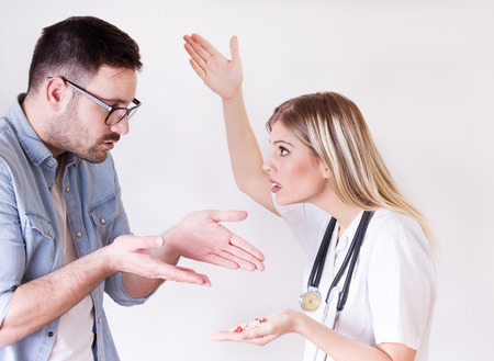 Male patient rejecting to take spoon full of pills from angry female doctor Stock Photo