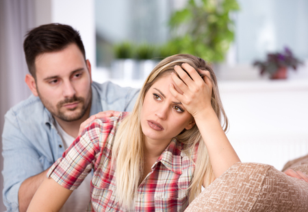 Young couple having problems in relationship, boyfriend feeling guilty. Sitting on sofa in living room