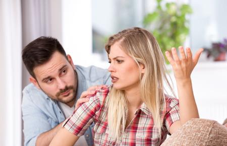 Jeune couple ayant des problèmes relationnels, son petit ami se sentant coupable. Assis sur un canapé dans le salon