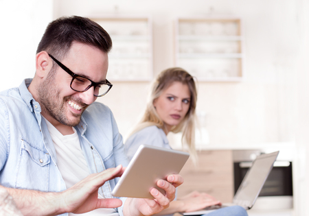 Young couple having issues in relationship. Man holding tablet and smiling and girlfriend look jealously in background