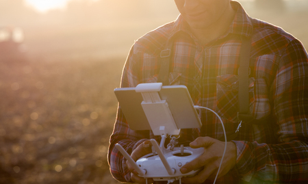 Close up of remote control with tablet for drone in farmers hands in field. High technology innovations for increasing productivity in agriculture Stock Photo