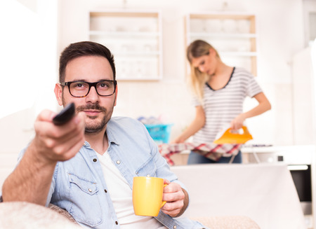Young handsome man sitting on sofa and holding tv remote control while wife ironing and doing chores in background