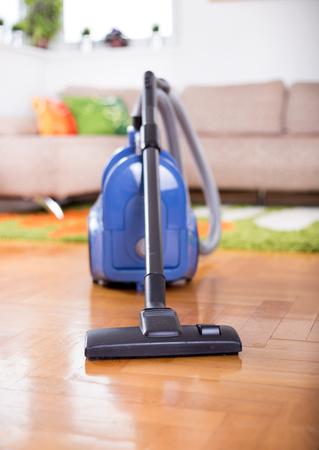 Blue vacuum cleaner standing on parquet floor in front of sofa in living room