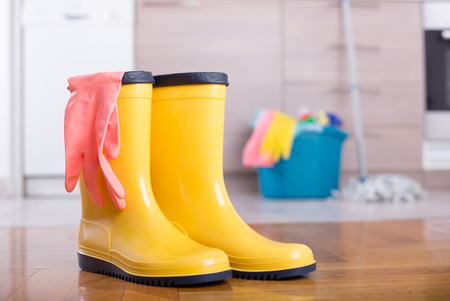Yellow gumboots on floor with bucket, mop and cleaning products in background in kitchen. Housekeeping service concept