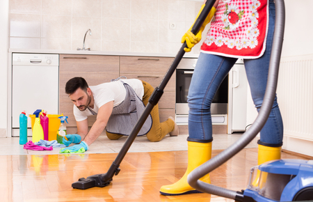 Young couple doing chores together. Man wiping floor on knees and girl hoovering floor Stock Photo