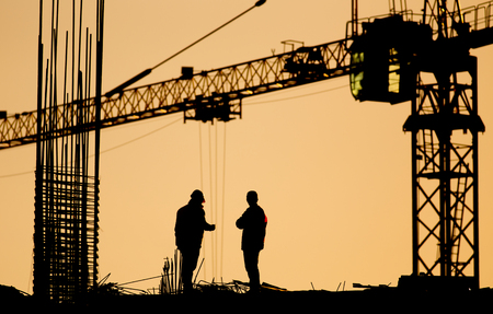 Engineer and worker on top of structure under construction at building site with crane in background, at sunset