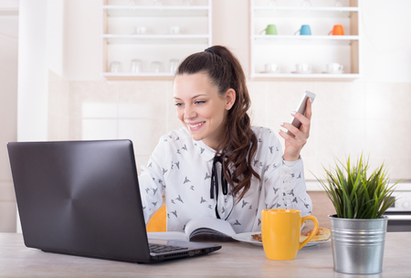 Smiling young woman working on laptop at kitchen table with cup of coffee and pizza beside her