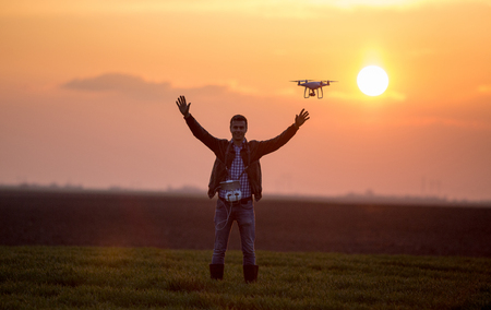 Satisfied farmer navigating drone in field. High technology innovations for increasing productivity in agriculture