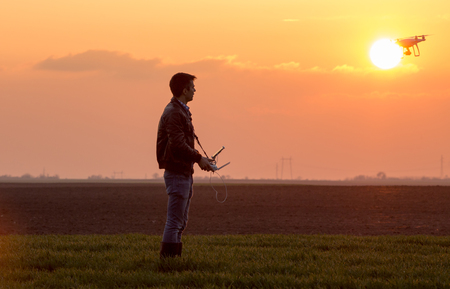 Farmer navigating drone in field. High technology innovations for increasing productivity in agriculture Stock Photo