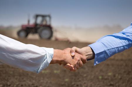 Zwei Geschäftsleute, die Hände im Feld mit Traktor schütteln, der im Hintergrund arbeitet. Agribusiness-Konzept