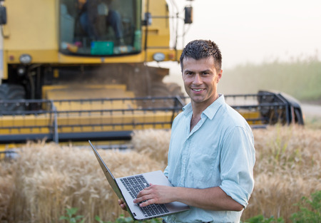 Happy young farmer engineer with laptop standing on wheat field while combine harvester working in background