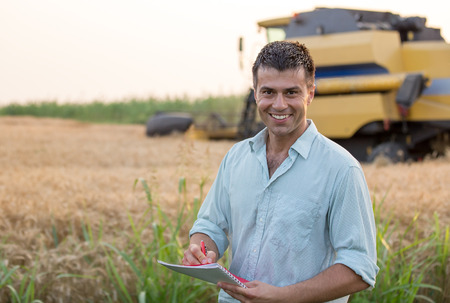 Happy young farmer engineer with notebook standing on wheat field while combine harvester working in background Stock fotó