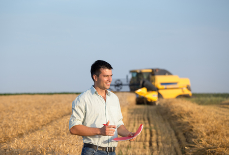 Happy young farmer engineer with notebook standing on wheat field while combine harvester working in background Archivio Fotografico