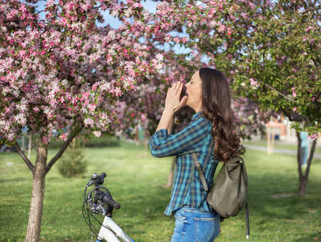 Young pretty girl sneezing in front of blooming tree. Spring allergy concept